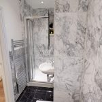 Grey marble huge tiles and white bathroom suite were used in this bathroom